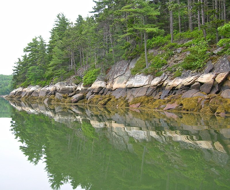 Reflections of the rocky shoreline in The Basin, a multi-fingered tidal cove in Phippsburg, are especially beautiful on a cloudy, calm day.