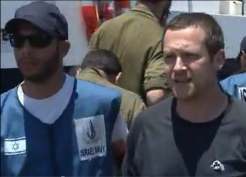 Scott Hamann, right, is shown being led away by an Israeli Navy guard. The picture is taken from a video posted on YouTube. Click the link below to see the whole video.