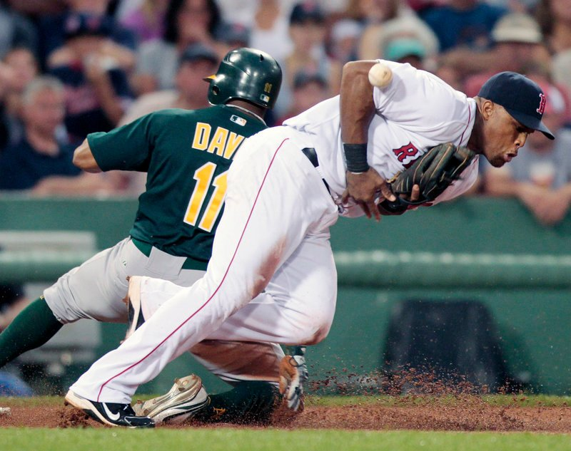 Rajai Davis of the Oakland Athletics slides safely into third base Tuesday night as Adrian Beltre of the Boston Red Sox attempts to control the ball during Boston's 9-4 victory at Fenway Park. The Red Sox have won 8 of 10.