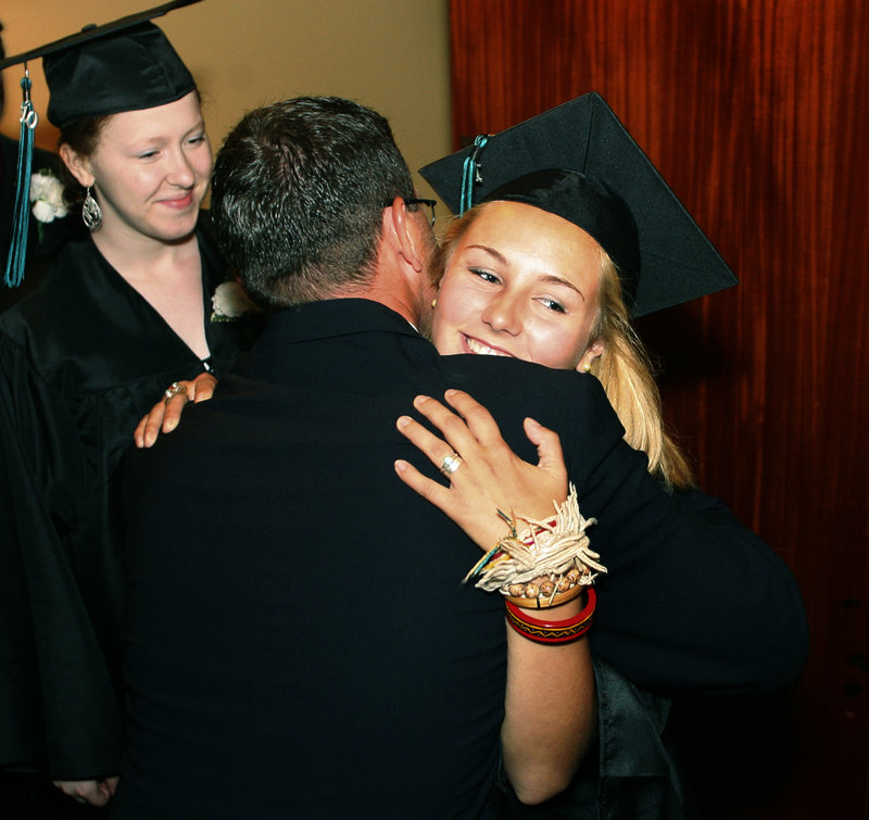Casco Bay High School teacher Scott Shibles hugs Taylor Boucher during the procession of graduates Wednesday at Merrill Auditorium in Portland.