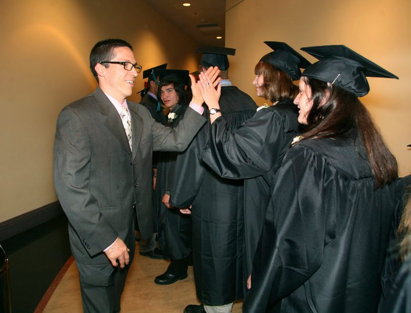 Casco Bay High School teacher Kevin Murray high-fives senior Charlotte McDonald before the start of the graduation ceremony Wednesday at Merrill Auditorium in Portland.