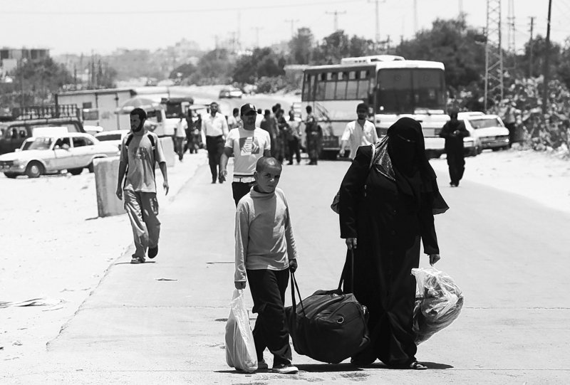Palestinians carry their luggage to the Rafah border crossing between Egypt and the southern Gaza Strip on Wednesday, after Egypt eased its blockade of Gaza following Israel's deadly naval raid on an aid flotilla bound for the blockaded Gaza Strip.