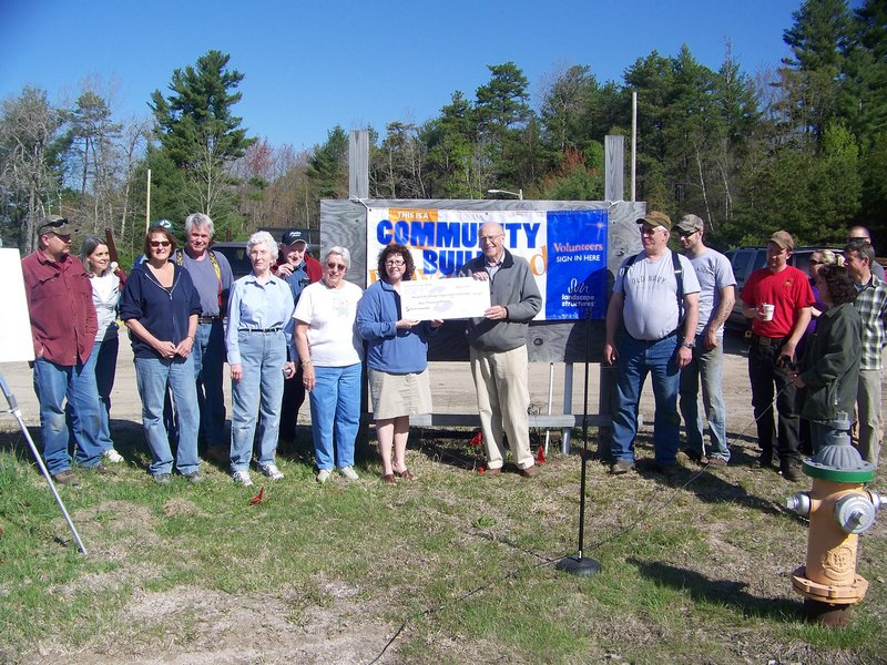 Norway Savings presents a $1,000 check to the Steep Falls Village Improvement Society to help with construction of a community park.