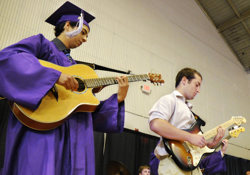 """Deering High School senior Jorge Barzallo, left, plays guitar while the senior class sings Journey's """"Don't Stop Believin'."""""""