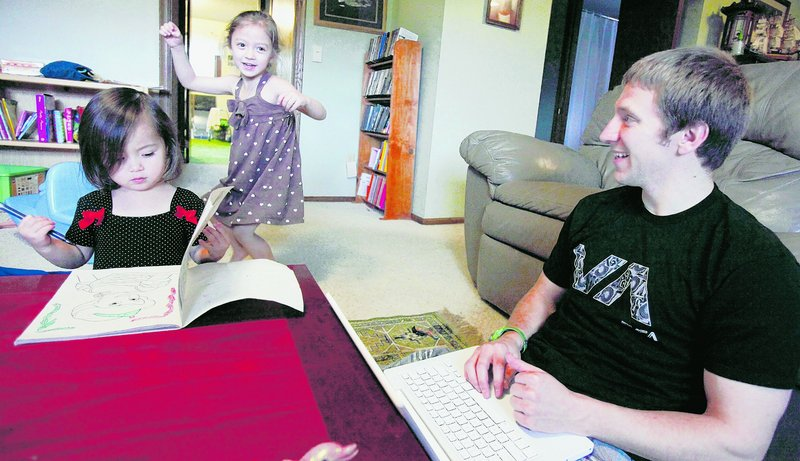 John Kay, a recent graduate of Pepperdine Law School, plays with his daughters Hana, left, and Autumn, while looking for jobs online. Kay had a job offer, but it was rescinded due to the sour economy.
