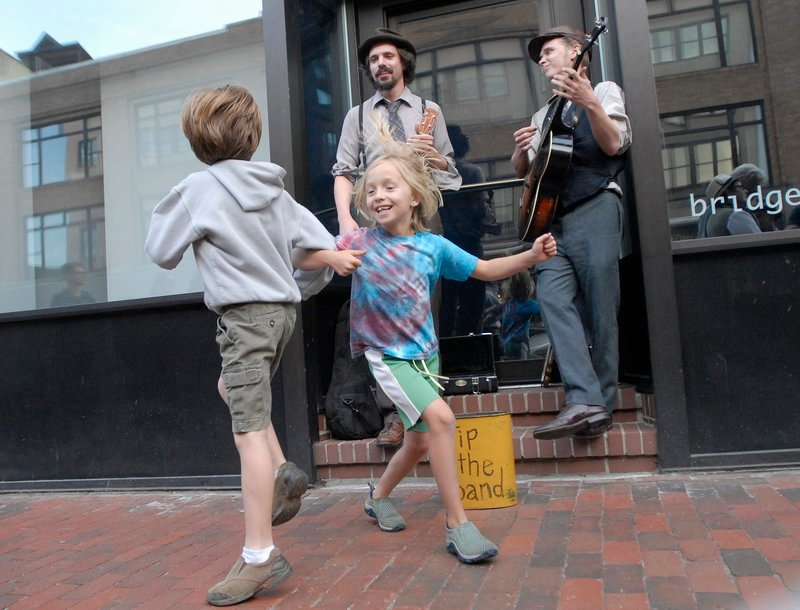 Carly Hagelin, 8, of Portland and Kieran Elliott, 7, of Portland dance as Tim Findler and Jimmy Dority of Portland perform on Congress Street during the First Friday Art Walk.