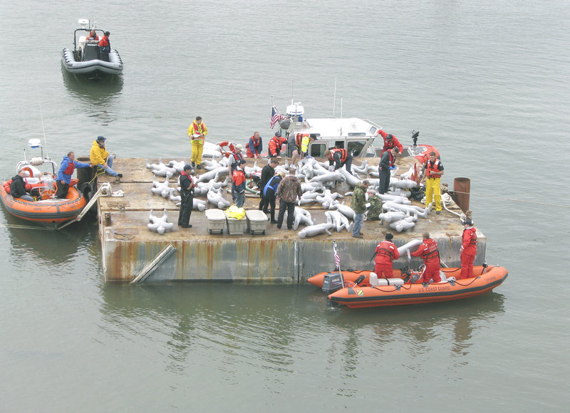 Emergency responders work at the 'crash scene,' a barge near the Veterans Memorial Bridge.