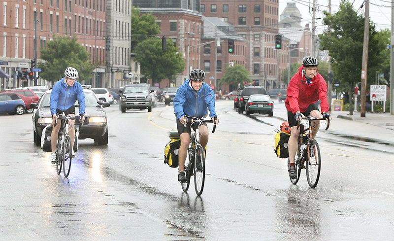 Pete Phipps, Daniel Marques and Joel Glover ride on Commercial Street as they leave Portland on Sunday morning for their trek across the country to Los Angeles.