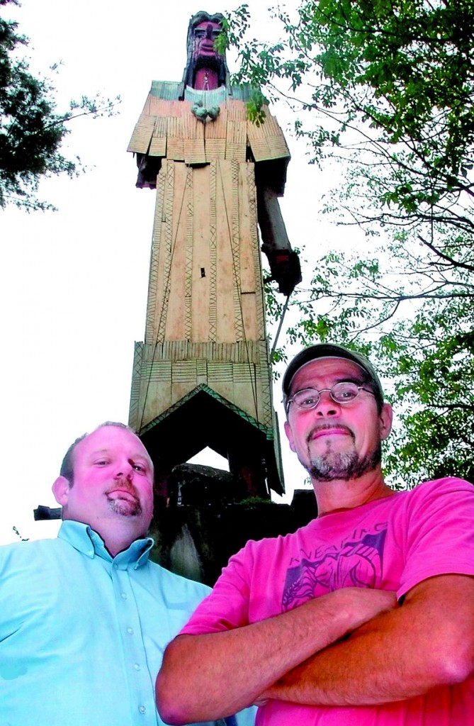 Cory King, left, executive director of the Skowhegan Area Chamber of Commerce, and cabinet maker Stephen Dionne pose beneath Bernard Langlais' Indian. Parts of the sculpture have been removed for restoration, which is Dionne's bailiwick.