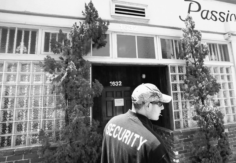 A security guard who declined to give his name stands outside House of Kush, a closed medical marijuana shop, Monday in the Eagle Rock area of Los Angeles.