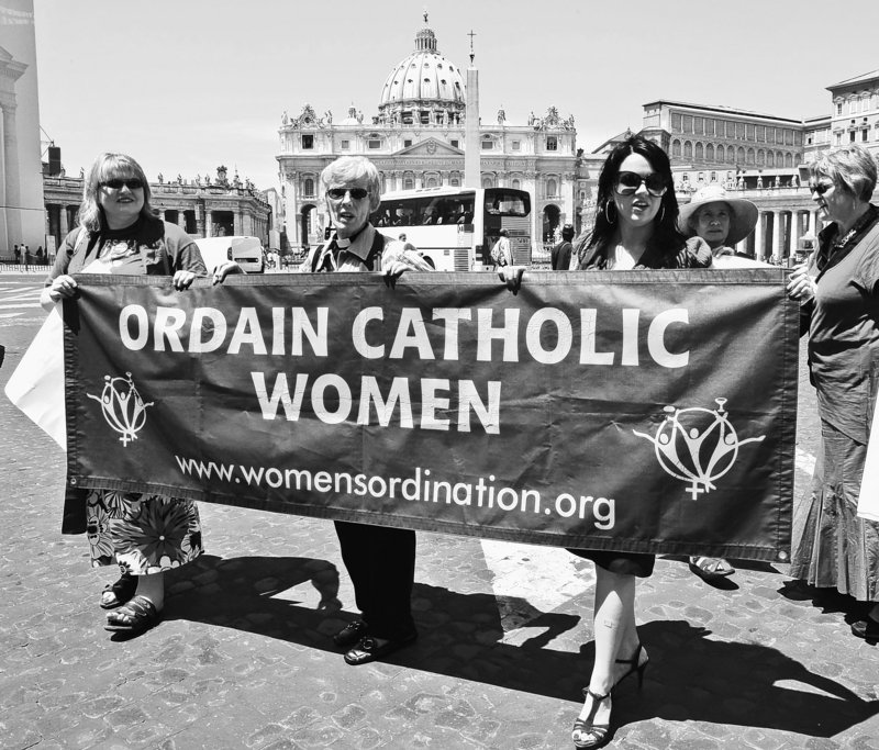 Representatives of the Women's Ordination Conference protest Tuesday in front of St. Peter's Basilica in Rome, with, from left, Therese Koturbash of Dauphin, Manitoba, Mary Ann Schoettly of Newton, N.J., and Erin Saiz Hanna of Washington, D.C. The protest took place on the eve of a rally marking the end of the Catholic Church's yearlong celebration of the priest.