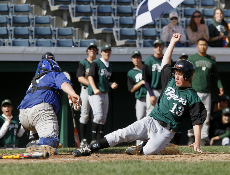 Charlie Laprade of Waynflete slides safely into home as OOB catcher Brandon Ouellette reaches for a wide throw. Ouellette also pitched three innings.