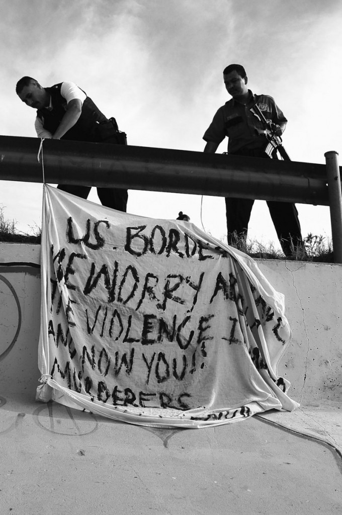 """The Associated Press One line for cutline goes to book asjfl;kjasdlk fjasdlaksjfl;kaks Mexican police bring down a banner that was placed near the site where 15 year old Sergio Adrian Hernandez Huereka was shot and killed by a U.S. border patrol agent a day earlier near the Paso del Norte international bridge in the northern border city of Ciudad Juarez, Mexico, Tuesday June 8, 2010. The banner says: """"U.S. Border Patrol: We are worried about the violence in Mexico and now you!! Murderers! Viva Mexico!"""" (AP Photo)"""