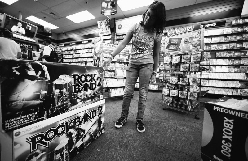 Video gamer Paulette Rivera, 13, checks a guitar for her video console at a Game Stop store in Los Angeles. Manufacturers will be unveiling new products next week at the Electronic Entertainment Expo.