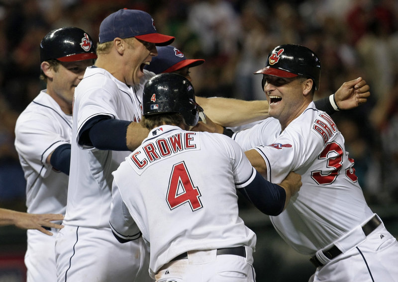 Russell Branyan is mobbed by his Cleveland Indians teammates Thursday night after looping a two-out, two-run single to right field off Daniel Bard to beat the Boston Red Sox, 8-7.