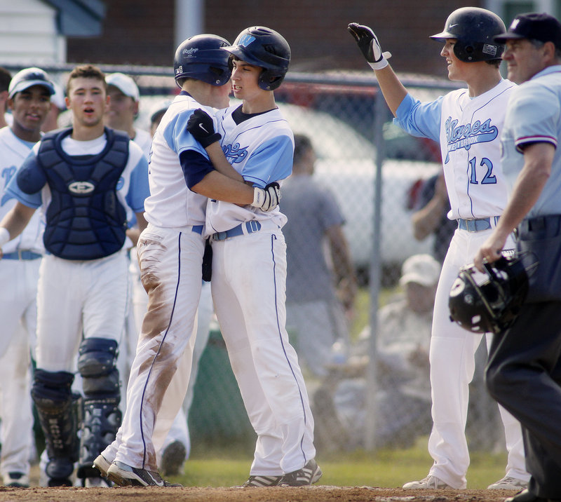 Sam Stauble, left, and Joe Quinlan of Westbrook celebrate Friday after scoring on a two-run double by Scott Heath in the third inning of the 4-0 victory against South Portland. The Blazes will play Deering in the semifinals today.