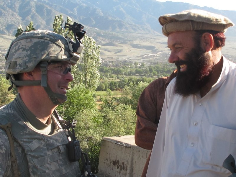 Bravo Company commander Capt. Paul Bosse of Auburn chats with a local elder during Saturday's search operation. No weapons were found, but a man suspected of Taliban ties was detained.