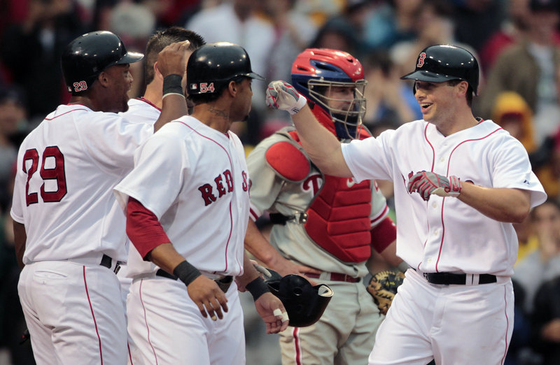 Daniel Nava, right, is greeted by Darnell McDonald, front, Adrian Beltre, left, and Jason Varitek after hitting a grand slam in the second inning Saturday.