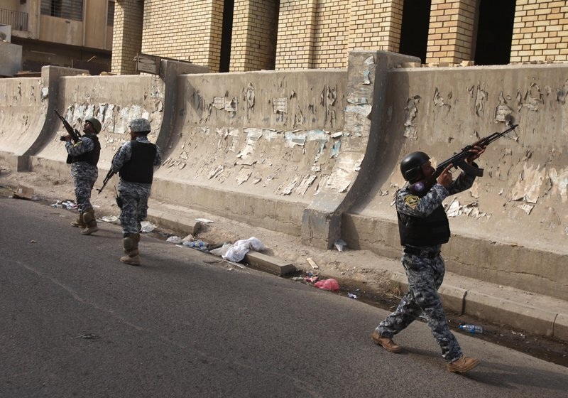Iraqi policemen prepare to secure the scene of a string of bombings near the Central Bank of Iraq in Baghdad on Sunday. Explosives-packed cars and roadside bombs killed dozens of people in an attack that targeted the Iraqi government's central bank.