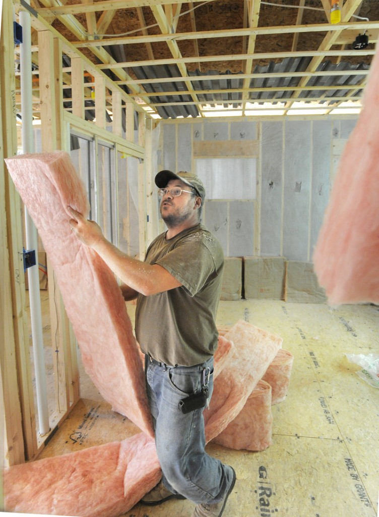 Daniel Gagnon of Lewiston installs insulation in a new home being built in Falmouth. Falmouth had adopted its own minimum energy standards for construction before the state made the new rules.