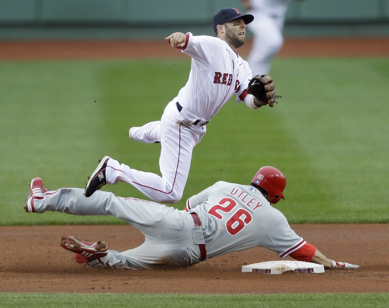 Boston's Dustin Pedroia leaps as he forces out Philadelphia's Chase Utley at second base on a double-play ball struck by Jayson Werth in the first inning Sunday at Fenway Park.