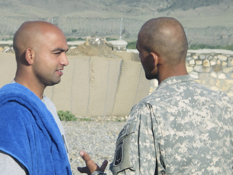 Pfc. Hamayon Ahadi of Biddeford, who was born in Kabul and moved to the United States at age 2, chats with a Bravo Company interpreter Monday at Combat Outpost Dand wa Patan.