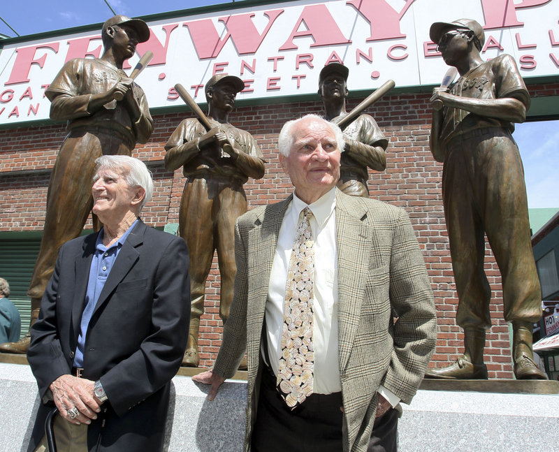 Red Sox legends Johnny Pesky, left, and Bobby Doerr stand before a statue outside Fenway Park depicting them with fellow longtime stars Ted Williams and Dom DiMaggio.