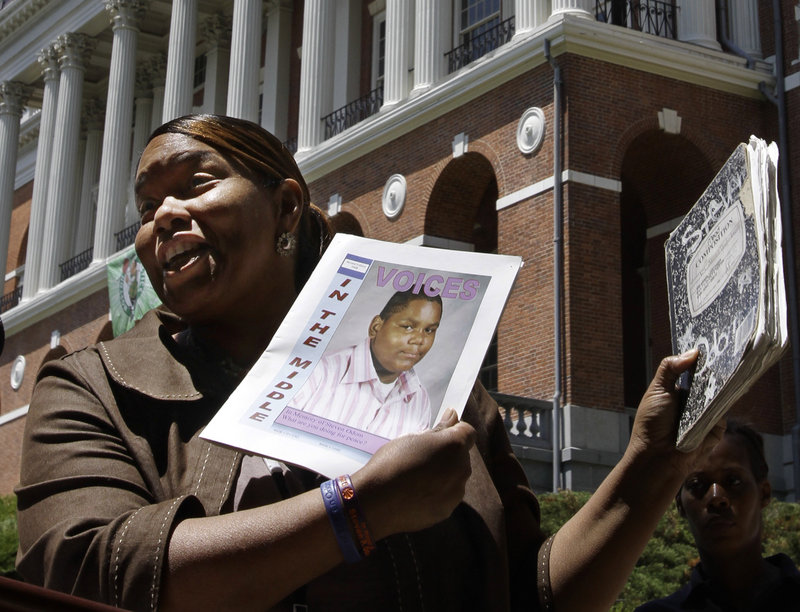 Kim Odom, mother of 13-year-old shooting victim Steven Odom, holds a photo of her son at a rally in front of the Statehouse in Boston on Tuesday. Odom supports a gun bill backed by Gov. Deval Patrick that would limit Massachusetts gun buyers to one firearm per month.