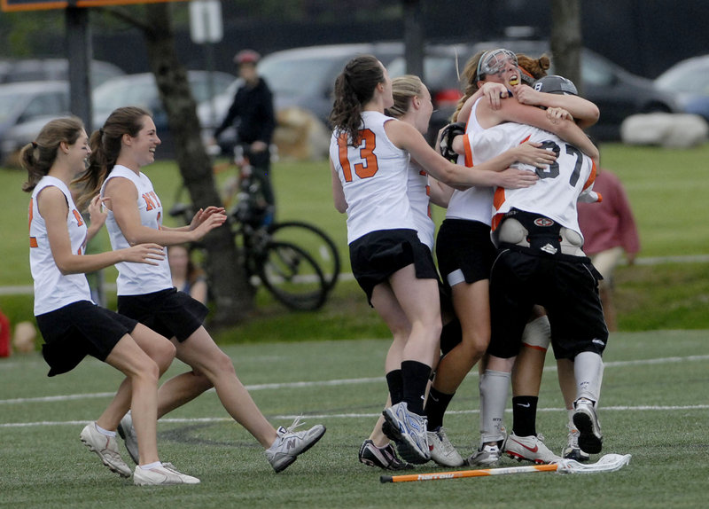 The North Yarmouth Academy girls' lacrosse team begins the celebration Wednesday after avenging two regular-season losses by beating Yarmouth 9-5 in a regional final.