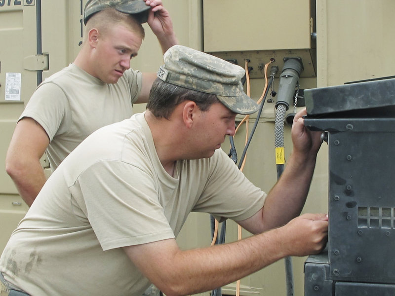 Spc. Jeffrey Pelletier of Waterville, foreground, and Pfc. Kevin Beal of Machias work on a faulty generator that gave out halfway through dinner preparations Wednesday for Maine Army National Guard troops at Combat Outpost Dand Wa Patan in Afghanistan. Moments later, they fired up the barbecue grill.