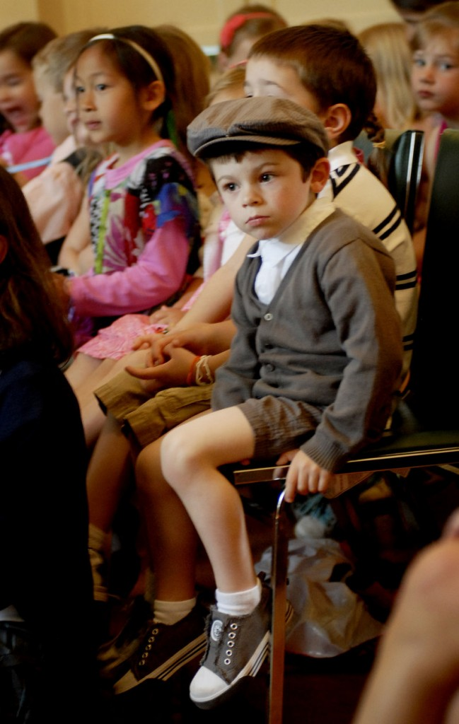 Louison Carribou, 3, a pre-schooler at the school, listens during end of year ceremonieson Thursday.