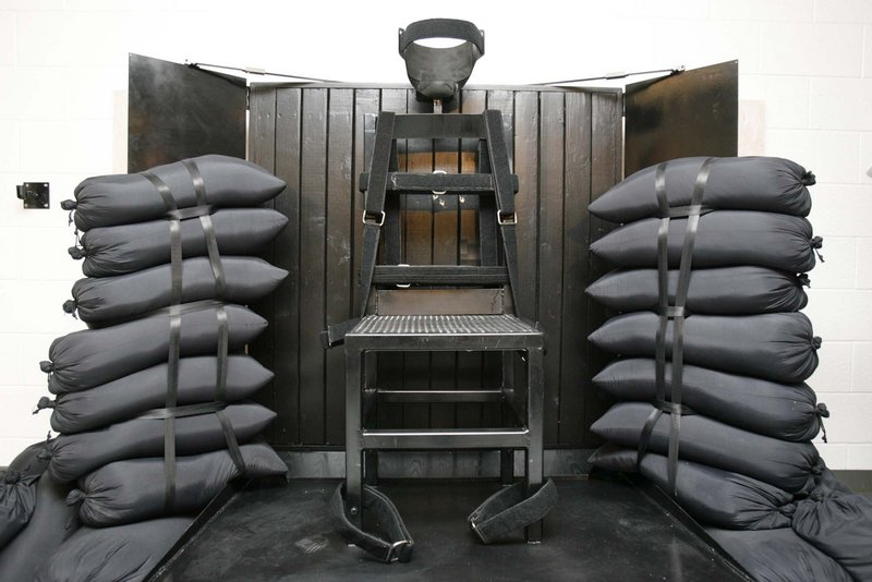 Inmate Ronnie Lee Gardner sat in this chair in the Utah State Prison as he was executed by firing squad early Friday. Bullet holes are visible in the wood panel behind the chair.