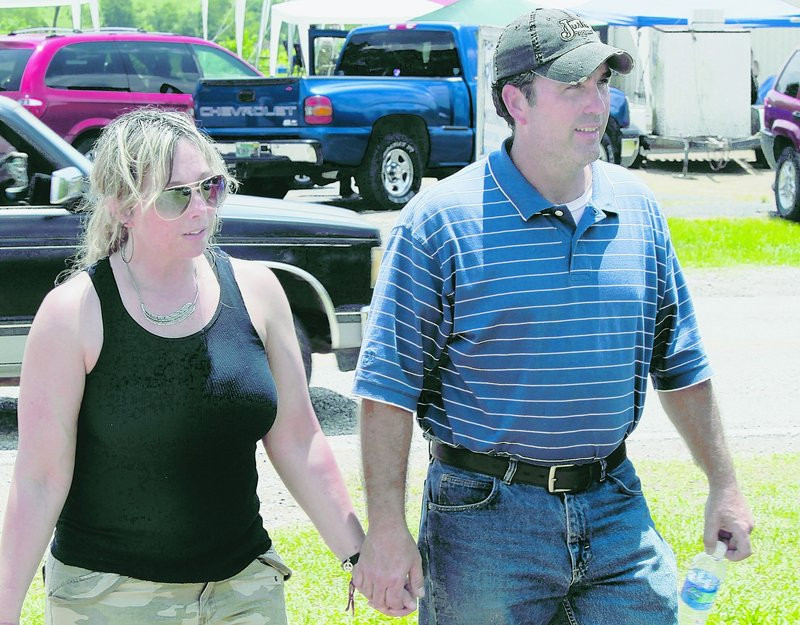 Pastor Graig Cowart and his wife, Andrea, who helped many families after the deadly flooding, walk from Pilgrim Rest Baptist Church in Lodi, Ark., last Sunday.