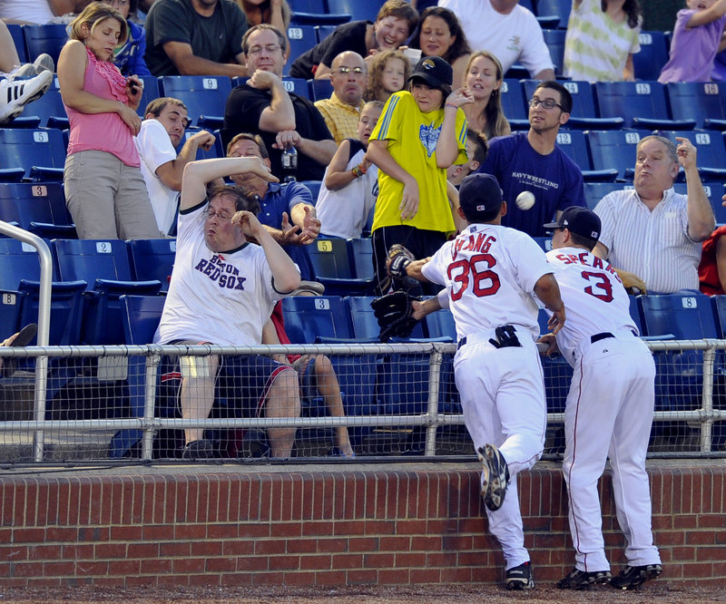 Fans take cover as Sea Dogs third baseman Ray Chang, left, and shortstop Nate Spears reach over the railing in an attempt to catch a foul ball. Chang drove in the winning run in the 10th inning as the Sea Dogs beat the Akron Aeros 8-7 Friday night at Hadlock Field.