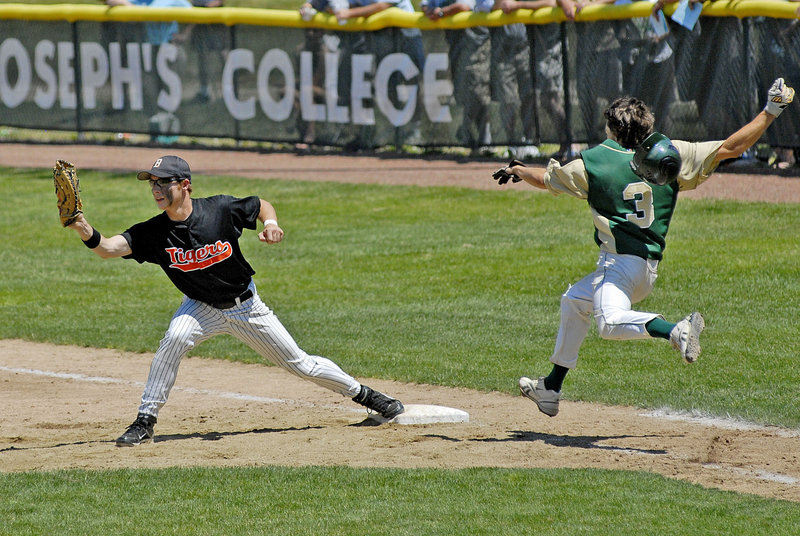 Biddeford first baseman Tyler Audie stretches for the ball for an out Saturday just before Cody Hadley of Oxford Hills reaches the bag. Oxford Hills won the Class A title, 1-0.