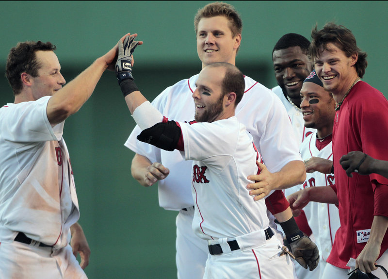 Boston's Dustin Pedroia, center, celebrates with teammates, from left, Daniel Nava, Jonathan Papelbon, David Ortiz, Darnell McDonald and Clay Buchholz after his walk-off RBI single in the ninth to beat the Dodgers 5-4 Saturday.