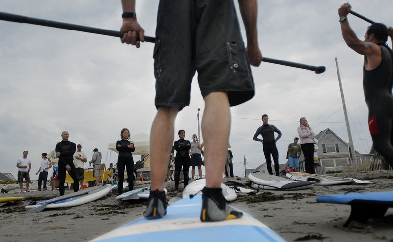 Surfers listen to instructors on stand-up paddling techniques during the International Surfing Day celebration.
