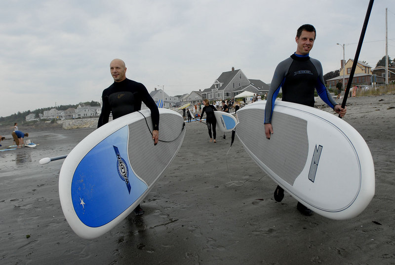 Greg Brown of Freeport, left, and Dylan Nickerson of Scarborough make their way toward the water while surfing at Higgins Beach in Scarborough during the sixth annual International Surfing Day celebration Sunday.