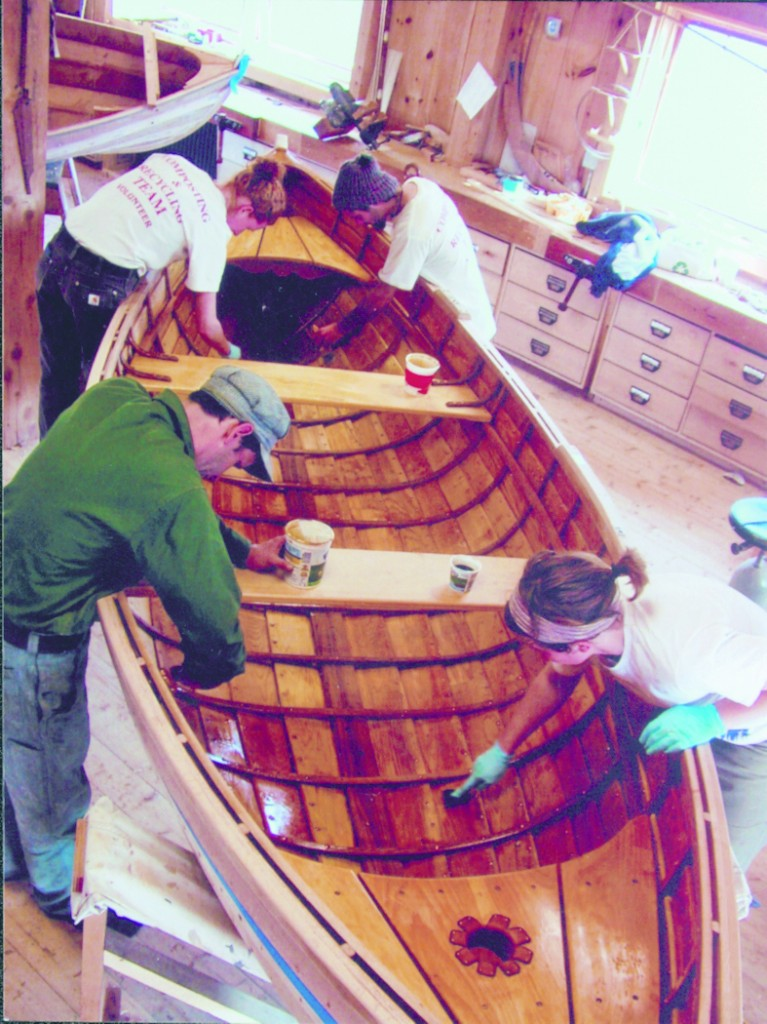 A recent class at the boat shop puts final touches on their wooden creation.