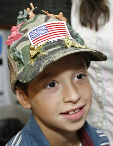 David Morales models the hat decorated with toy soldiers that got him in trouble in school.