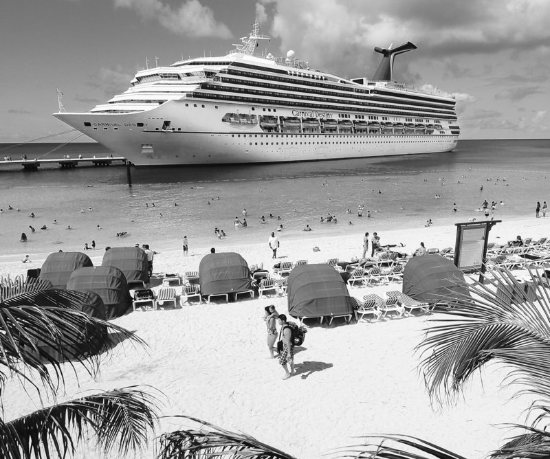 CARNIVAL PROFIT DIPS: Passengers aboard the Carnival Destiny relax on the beach at the Grand Turk Cruise Terminal in the Turks and Caicos Islands. A 64 percent increase in fuel prices hurt Carnival Corp.'s second-quarter net income, which fell more than 4 percent to $252 million.