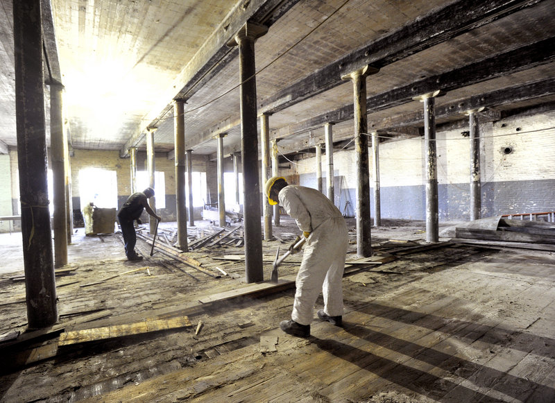 A work crew removes old flooring at the former Bates Mill in Lewiston, soon to be the home of Baxter Brewing Co.