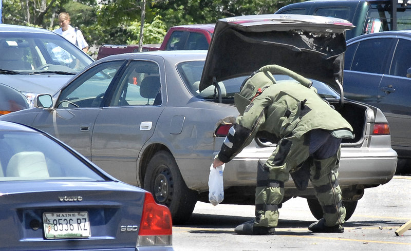 A Maine State Police bomb squad member removes a bag on Friday from the trunk of a Toyota Camry parked in the front parking lot at Southern Maine Medical Center in Biddeford. Authorities said they recovered five pipe bombs from the vehicle parked there by an Alfred man.