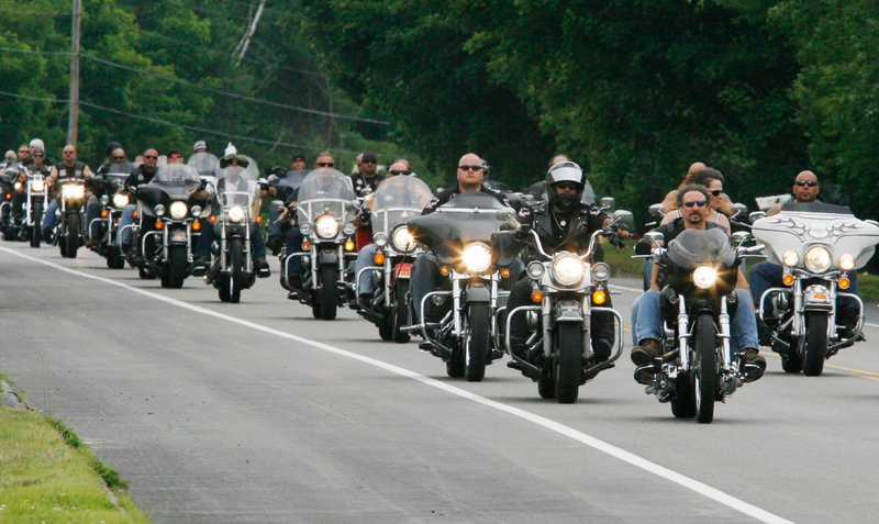 Members of the Outlaws motorcycle club, joined by members from other clubs, ride through Hollis Center on Saturday on their way to a memorial service for Thomas Mayne, a club leader who was killed June 15 during a shootout with federal agents in Old Orchard Beach.