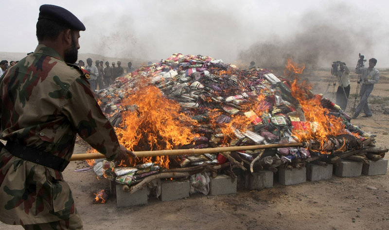Journalists take photos as authorities burn a pile of confiscated drugs outside Karachi on Saturday. Officials say Pakistani media badly misrepresent the United States in their news reports.