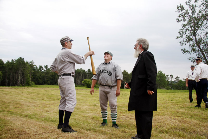"""Umpire Jeff """"Gray Beard"""" Peart of Manchester, Mass., right, watches as Mark """"Limelight"""" Rochman of Augusta, left, wins the bat toss for Dirigo over Brian """"Cappy"""" Sheehy of Methuen, Mass., to decide first-ups."""
