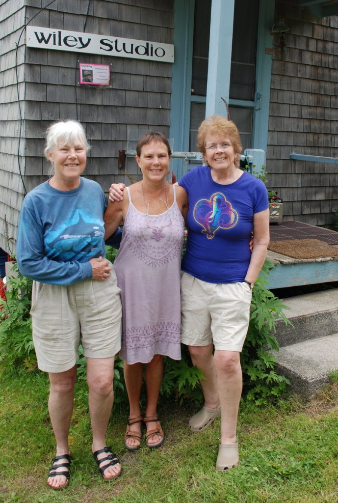 "Fred Wiley's daughters, Dede Wiley, left, and Mim McLellan, center, pose with their ""wicked good stepmother,"" Faryl Wiley, outside his studio. Fred Wiley first came to Monhegan in the 1960s and loved showing ""first timers"" around the island."