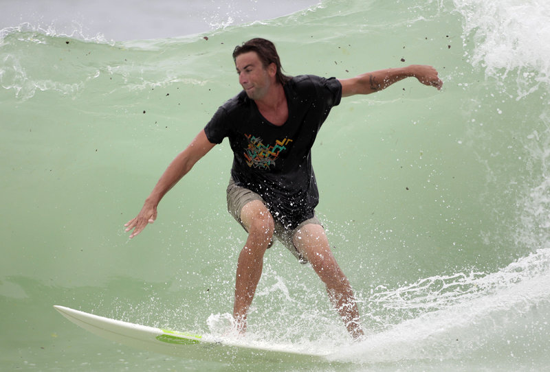 Tar balls can be seen in the water as Grayson Flowers surfs in waves stirred up by Tropical Storm Alex in Destin, Fla., on Monday. Meanwhile, BP is working on equipment that, if a hurricane threatens, can be stopped and restarted in two days instead of five.