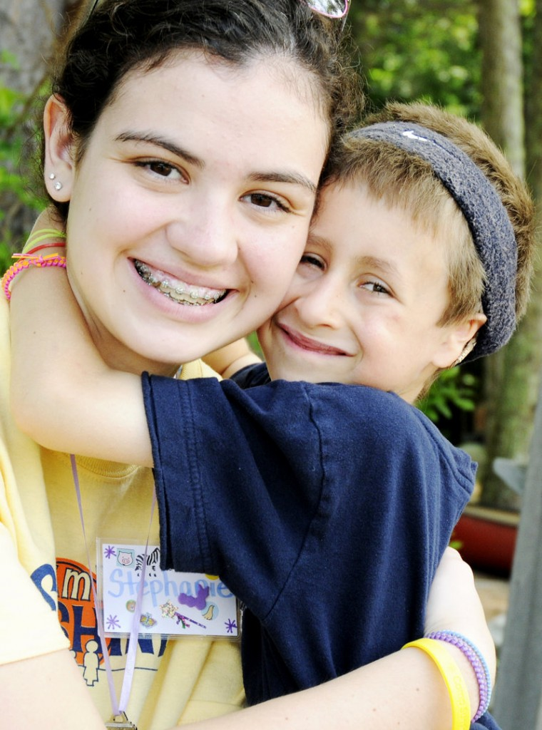 Camp Sunshine volunteer Stephanie Reeves gets a hug from 7-year-old Wesley Young on Tuesday at the campground on the north shore of Sebago Lake. Wesley, of Gorham, was diagnosed with Fanconi anemia when he was a year old and has attended the weeklong camp for children with the rare blood disorder every year since.