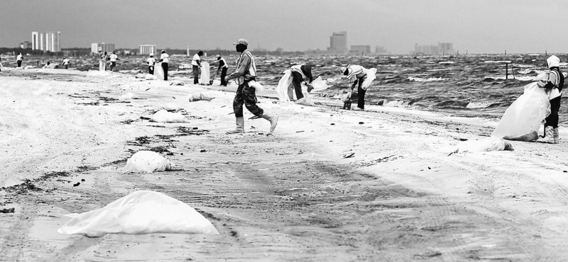 A cleanup crew works to remove tar balls from a Gulfport, Miss., beach Tuesday. From Florida to Louisiana, efforts to skim oil from the water were halted as waves churned by Tropical Storm Alex reached heights of 12 feet in parts of the Gulf. The loss of skimming work combined with 25-mph winds driving water into the coast left beaches vulnerable to being coated with oil.